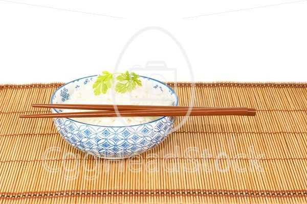 Bowl of rice with chopsticks against white backgrond - EggHeadStock
