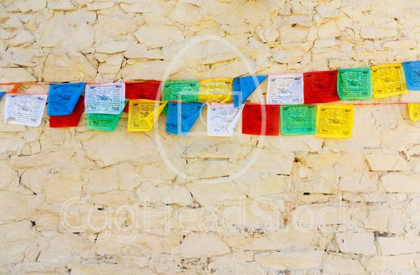 Buddhist tibetan prayer flags against wall - EggHeadStock