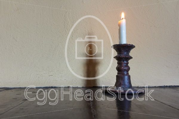 Burning candle in old candlestick - EggHeadStock