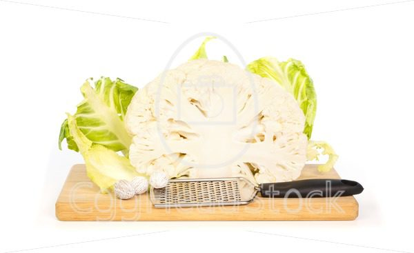 Cauliflower and nutmeg  and grater on a chopping board - EggHeadStock