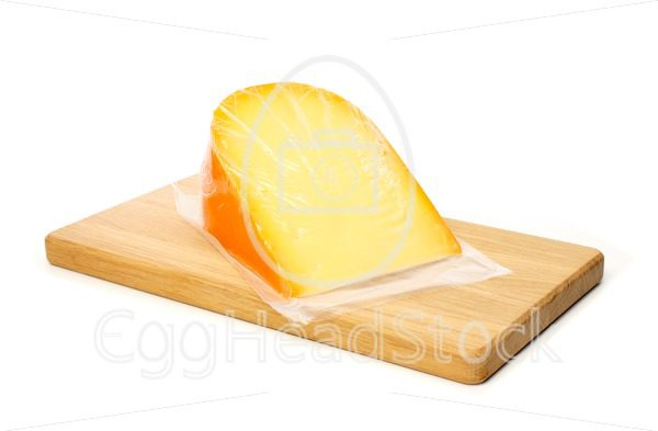 Cheese in vacuum packing on cutting board - EggHeadStock