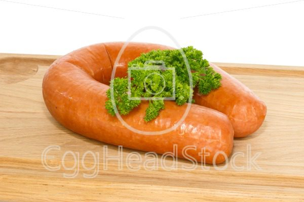 Dutch smoked sausage on a cutting board garnished with curly parsley - EggHeadStock