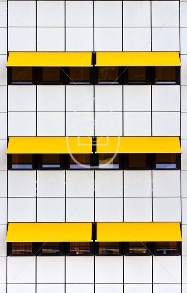 Facade with white tiles and yellow awnings - EggHeadStock