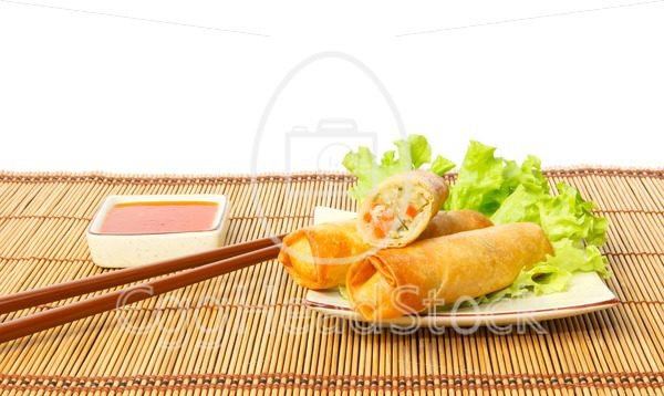 Fried spring rolls on a plate against white background - EggHeadStock
