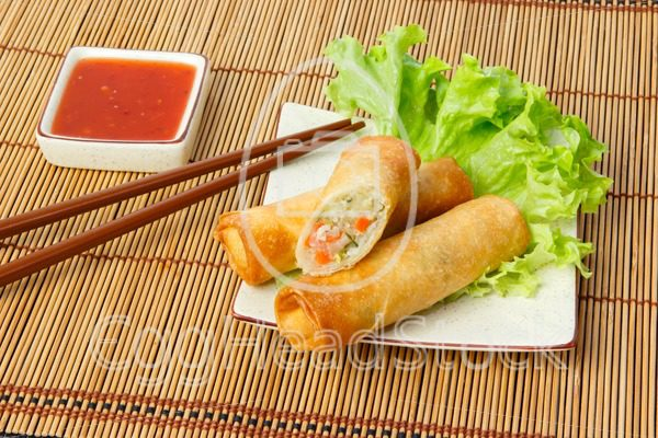 Fried spring rolls, one cut, on a plate - EggHeadStock