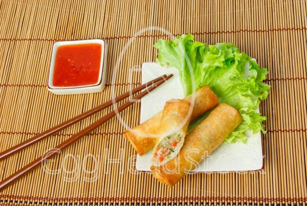 Fried spring rolls, one cut, on a plate with chopsticks - EggHeadStock