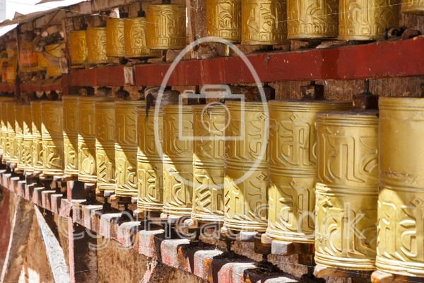 Gold colored Buddhist prayer wheels in Lhasa, Tibet - EggHeadStock