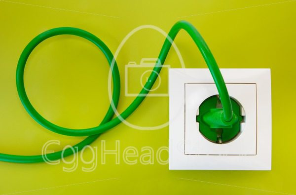 Green power plug into white power socket - EggHeadStock