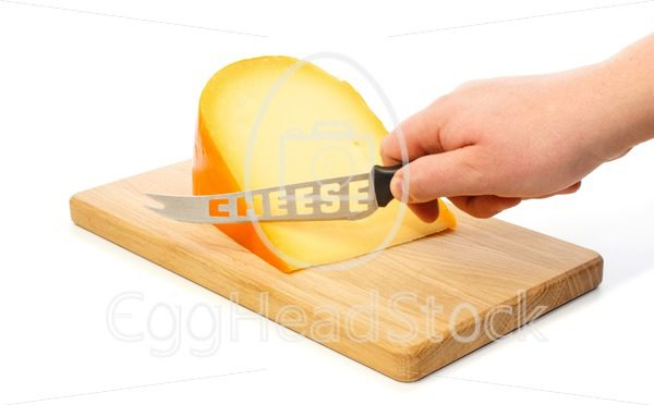 Hand cuts with knife the cheese on a cutting board - EggHeadStock