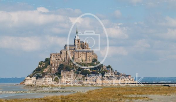 Le Mont Saint-Michel with tourists walking across the new bridge - EggHeadStock