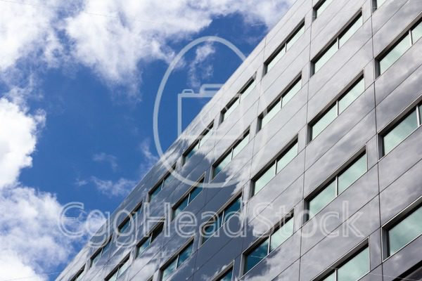 Office building reflects the cloudy sky - EggHeadStock