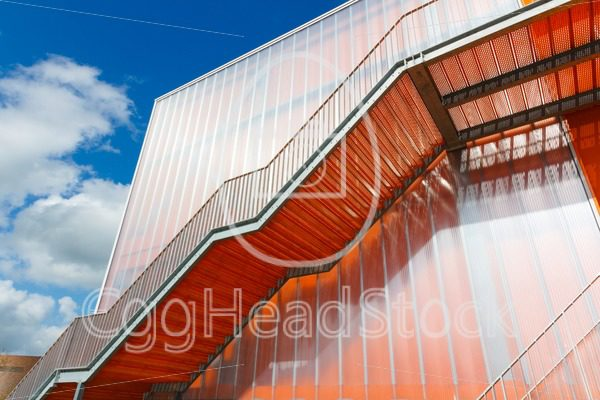 Orange stairs on the outside of modern building - EggHeadStock