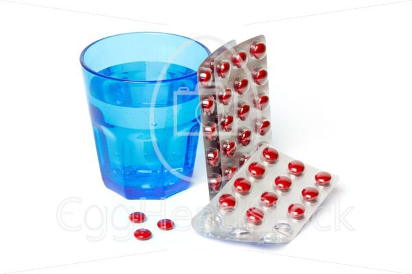 Pill strips and a blue glass with water - EggHeadStock