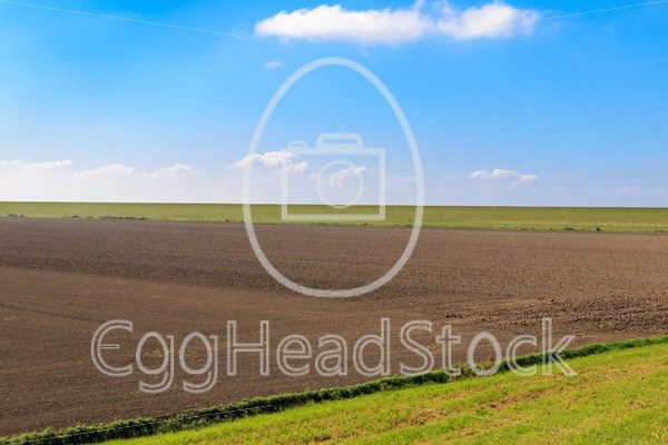 Ploughed field with protective dike in East Frisia, Germany - EggHeadStock