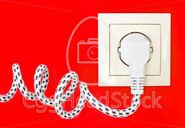 Power cord and power socket against a red background - EggHeadStock