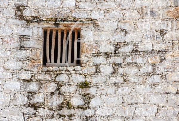 Prison cell window with wooden bars in a white brick wall - EggHeadStock