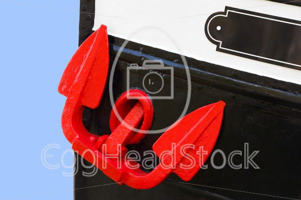 Red hoisted anchor on boat - EggHeadStock