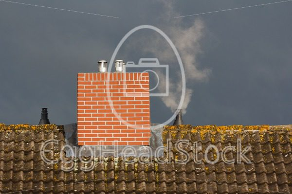 Roof and chimney against the background of bad weather - EggHeadStock