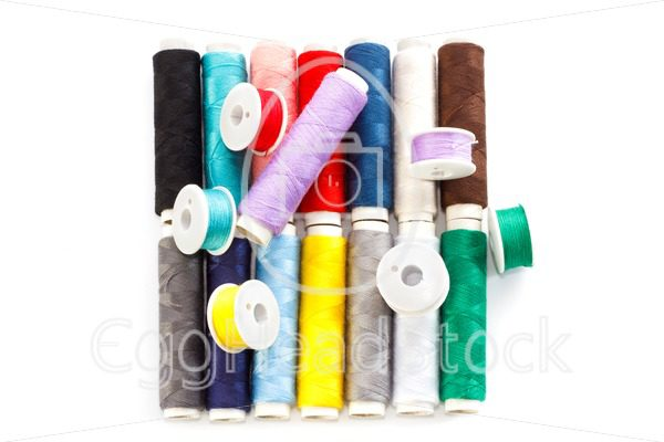 Several multicolored bobbins and coils with sewing thread - EggHeadStock