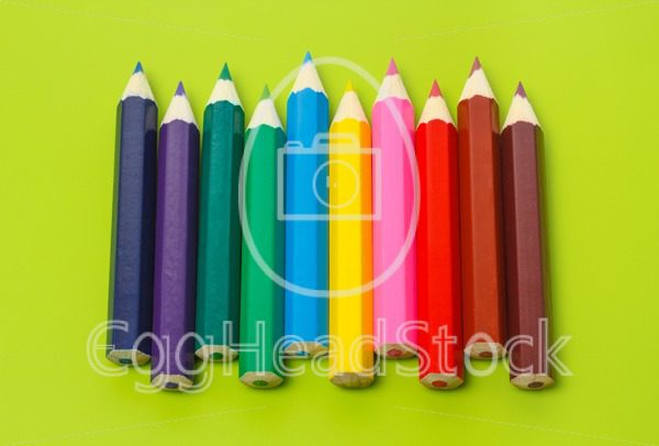 Small crayons in a row in rainbow colors - EggHeadStock