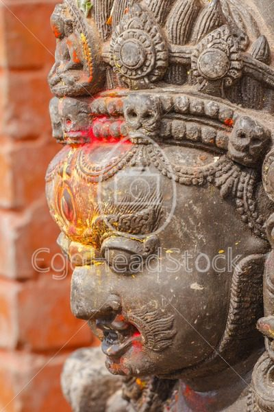 Statue of the wrathful deity Mahakala marked with colored powders at the religious Swayambhunath site or Monkey Temple in Kathmandu, Nepal - EggHeadStock