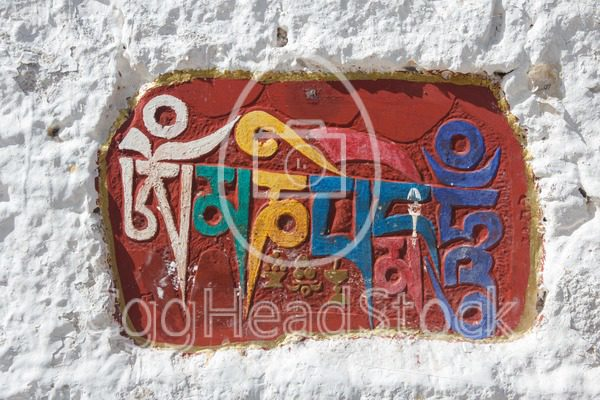 The Sanskrit mantra 'Om mani padme hum' inscribed and painted as a mani stone on a recess in a wall of the Potala Palace in Lhasa - EggHeadStock
