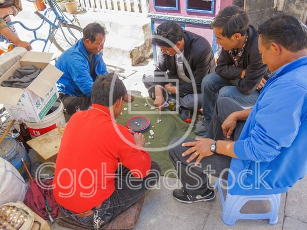 Tibetan men play a dice game  on the street in Lhasa, Tibet - EggHeadStock