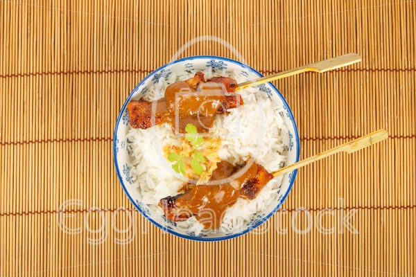 Top view of a bowl of rice with pork satay - EggHeadStock