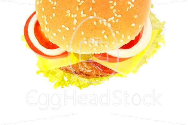 Top view of a burger with cheese, pickles, onion, tomato and sauce - EggHeadStock
