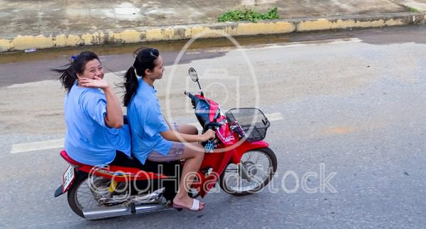 Two girls on a motorcycle in Thailand - EggHeadStock