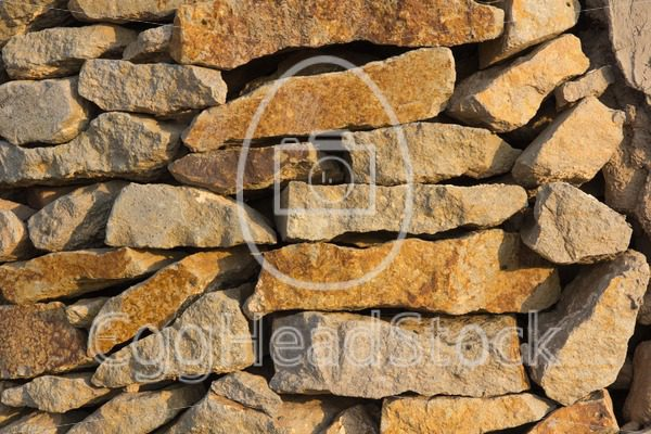 Wall made of natural stone in the evening sun - EggHeadStock