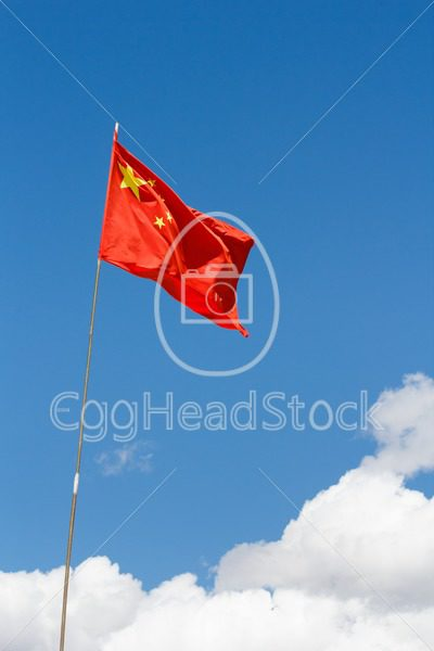Waving Chinese flag against blue sky - EggHeadStock