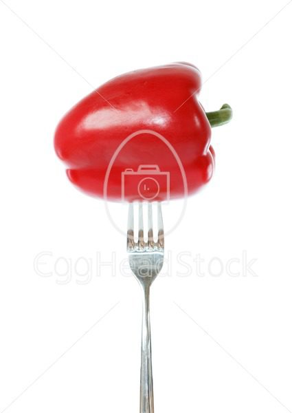 Whole red bell pepper pinned on a fork - EggHeadStock
