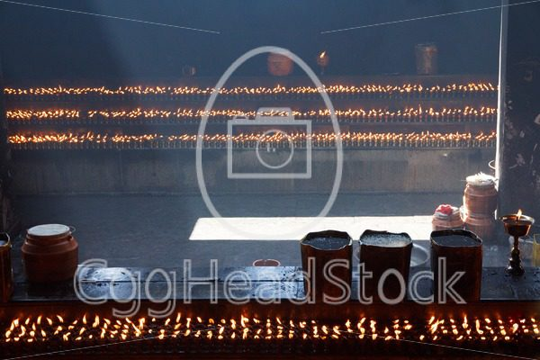 Yak butter lamps in small building at the entrance of Jokhang Temple, Lhasa, Tibet - EggHeadStock