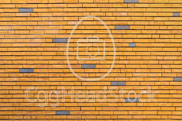 Yellow brick wall interspersed with some gray bricks - EggHeadStock