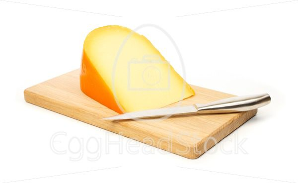 Yellow cheese and kitchen knife on a cutting board - EggHeadStock