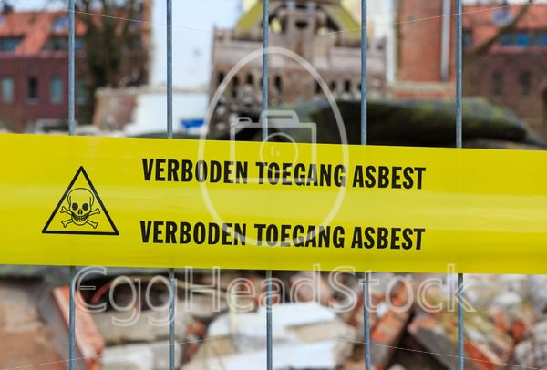 Yellow tape on fence with Dutch text 'no trespassing asbestos' - EggHeadStock