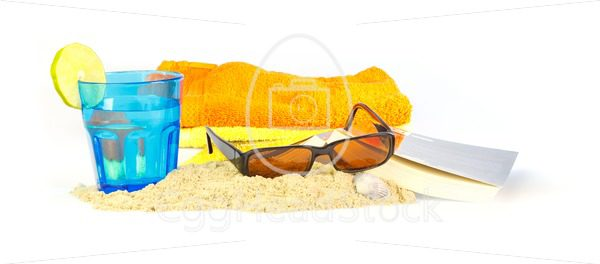 Holiday on the beach with towels, sunglasses, a book and a drink - EggHeadStock