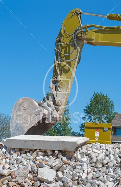 Arm of an excavator on a demolished building - EggHeadStock