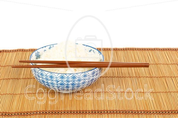 Bowl of rice with chopsticks and table mat against white backgrond - EggHeadStock