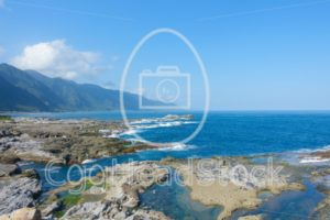 Rocky Taiwanese east coast with mountains in the background - EggHeadStock