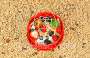 Mixed berries with yogurt and muesli in a red bowl. - EggHeadStock
