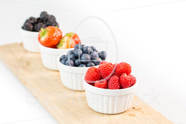 Raspberries, blueberries, strawberries and blackberries on a cutting board - EggHeadStock