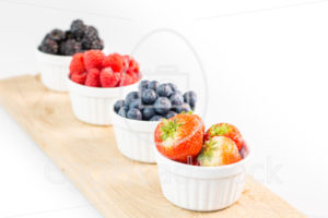 Strawberries, blueberries, raspberries and blackberries on a cutting board - EggHeadStock