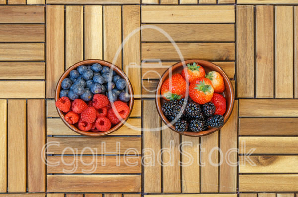 Top view of raspberries, blueberries, strawberries and blackberries in a terracotta bowl - EggHeadStock