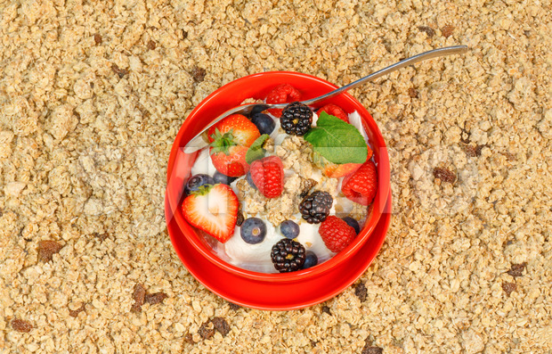 Mixed berries with yogurt and muesli in a red bowl. Stock Photo