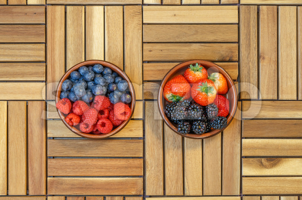 Top view of raspberries, blueberries, strawberries and blackberries in a terracotta bowl Stock Photo