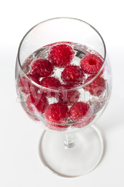 Raspberries in a wine glass with water Stock Photo