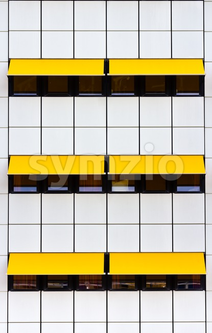 Crop of modern facade with white tiles and yellow awnings