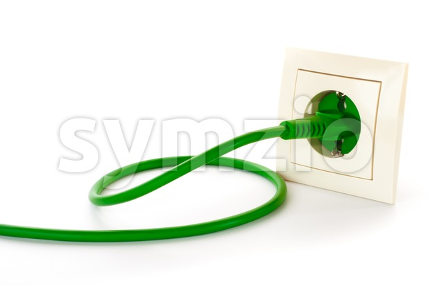 Green power plug into power outlet Stock Photo